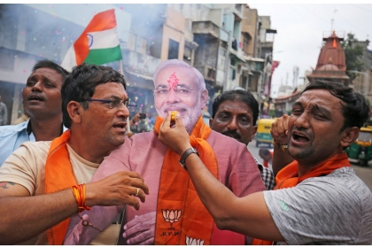 印度總理莫迪的支持者,五日在古吉拉特邦艾哈邁達巴德市拿著莫迪的立牌,並作勢餵莫迪吃甜餅,慶祝政府取消喀什米爾的特殊地位。(路透)
