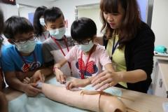 【媒體報導】學童變身「實習醫生」 愛興暑期營學縫豬皮、模擬抽血