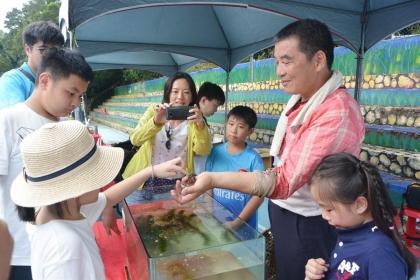【中時】小朋友對於水族箱裡的水生動物十分好奇,在地農民向他們講解生態奧妙。(巫靜婷攝)