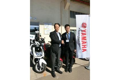 中興大學代表李明安同學(右)與台灣山葉機車公司武田總經理在捐贈機車前合影