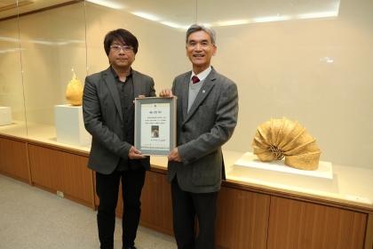 陳冠勳(左)捐贈作品「玀」(圖中右作品)予興大,興大校長薛富盛(右)致贈感謝狀
