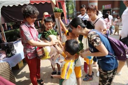 【自由時報】小朋友拿著自己種的蔬菜,向民眾推銷。(記者蔡淑媛翻攝)