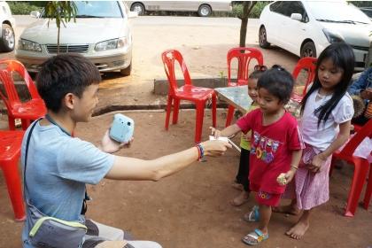 劉松旺至柬埔寨旅行,用拍立得幫當地孩童拍照。
