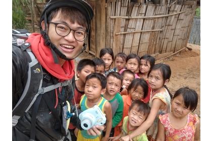 劉松旺至越南旅行,用拍立得幫當地孩童拍照。