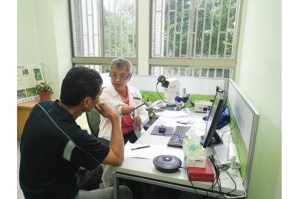 興大植物教學醫院找來專精各領域的教授組成實力堅強的駐診醫師團隊,圖為昆蟲系教授唐立正為農民看診情形。(圖片提供/興大植物教學醫院)