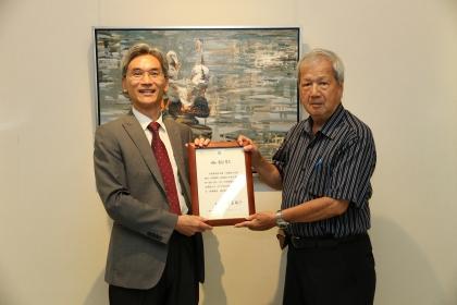 興大校長薛富盛(左)頒發感謝狀給畫家倪朝龍,感謝其贈送一幅畫作「愛在中興湖」(圖中掛畫)給興大藝術中心典藏
