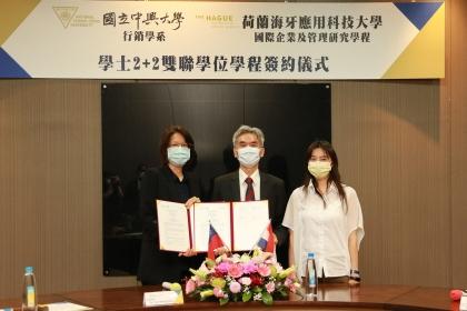 興大校長薛富盛(中)與行銷學系主任魯真(左)代表簽約,國際長張嘉玲(右)擔任見證