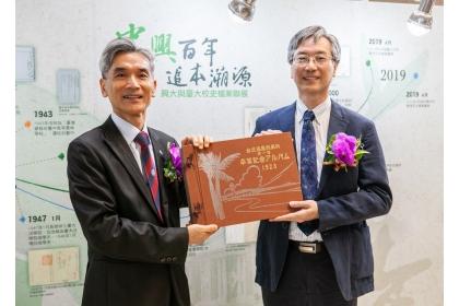 興大校長薛富盛(左)與臺大副總務長徐炳義(右)共同拿1928年台北高農林學科畢業紀念冊合影